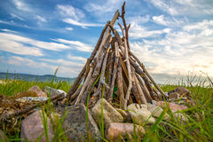 Bonfire of wood on the beach near the sea. around the decorated stones. stock image