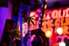 Bong e folha da marijuana do ouro na janela da loja fotos de stock royalty free
