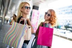 Bonheur, amis, achats et jeunes femmes de concept-sourire d'amusement avec des sacs ? provisions image libre de droits