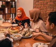 Bonheur de famille de hijrah quand appréciez la consommation iftar ensemble image stock