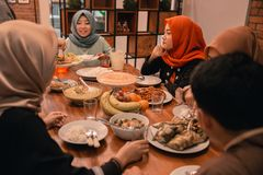 Bonheur de famille de hijrah quand appréciez la consommation iftar ensemble photographie stock