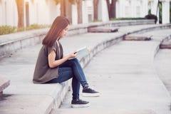 Bonheur de livre de lecture de femmes et éducation de l'adolescence asiatiques de sourire à l'université Photo libre de droits