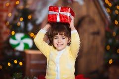 Bonheur de Noël Petite fille de sourire heureuse tenant le boîte-cadeau de Noël Photos stock