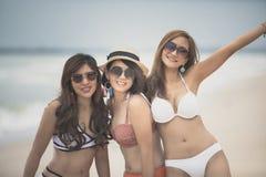 Bonheur de sourire toothy de port de visage de maillot de bain de belle femme asiatique gaie au bord de la mer photographie stock
