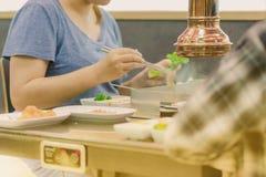 Bonheur Enjoy mangeant de la nourriture célèbre traditionnelle coréenne de BBQ avec la famille dans un restaurant coréen photographie stock libre de droits