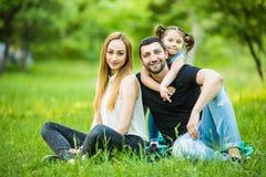 Bonheur et harmonie dans la vie de famille Concept de la famille heureux Jeunes mère et père avec leur fille en parc Famille heur Photographie stock