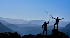 Bonheur et la lutte de monter la crête de montagne Images libres de droits