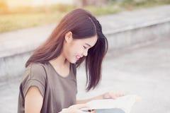 Bonheur et sourire de l'adolescence asiatiques de livre de lecture d'étudiante Photos stock