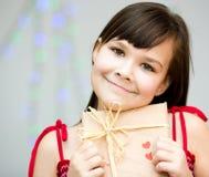 Bonheur - fille de sourire avec le coeur rouge Photographie stock libre de droits
