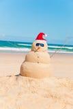 Bonhomme de neige anti-calorique s'exposant au soleil sur la plage Photo libre de droits