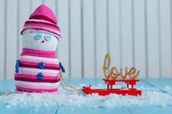 Bonhomme de neige appréciant un tour de traîneau avec le mot AMOUR Photographie stock