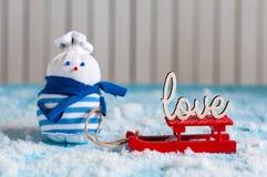 Bonhomme de neige appréciant un tour de traîneau avec le mot AMOUR Image libre de droits