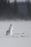 Bonhomme de neige au milieu d'un lac avec des pêcheurs de glace à l'arrière-plan Images libres de droits