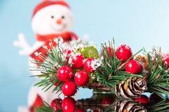 Bonhomme de neige avec la belle guirlande de Noël sur une surface bleue de miroir, décoration traditionnelle pendant la nouvelle  photos stock
