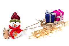Bonhomme de neige avec le traîneau, l'arbre de Noël et les cadeaux Photographie stock libre de droits