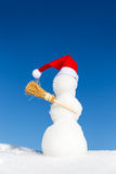 Bonhomme de neige avec un chapeau aigu et un balai dans la neige Photographie stock