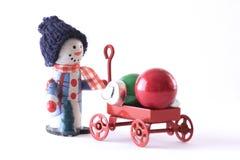 Bonhomme de neige avec un chariot des boules de Noël sur le fond blanc photographie stock libre de droits