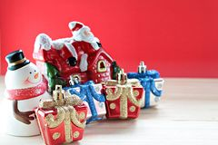 Bonhomme de neige, boîte de cadeaux de Noël ou présents et maison mignons de Santa Claus sur le bois, fond rouge Image libre de droits