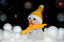 Bonhomme de neige dans la neige avec des boules de neige avec des feux d'artifice Images stock