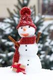 Bonhomme de neige dans le chapeau et l'écharpe de laine avec le cadeau pour le jour de valentines, concept saisonnier Photo libre de droits