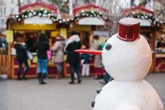 Bonhomme de neige dans le premier plan, sur le marché de Noël de fond Photo conceptuelle de la célébration de Noël Images stock