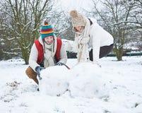 Bonhomme de neige de bâtiment de couples en hiver Images stock