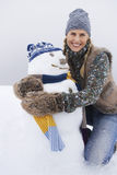 Bonhomme de neige de embrassement de jeune femme heureuse Images libres de droits