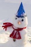 Bonhomme de neige de fond de paysage d'hiver dans une écharpe et un chapeau lumineux sur la neige Images libres de droits