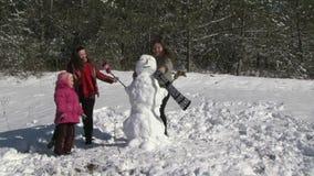 Bonhomme de neige de fondation d'une famille dans le jardin banque de vidéos