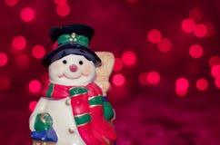 Bonhomme de neige en céramique sur le fond rouge de bokeh photos libres de droits