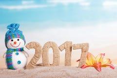 Bonhomme de neige 2017 et fleur d'inscription en sable contre la mer Images libres de droits