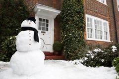 Bonhomme de neige et maison Photographie stock libre de droits