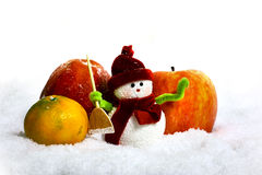 Bonhomme de neige et pommes dans la neige Photographie stock