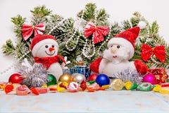 Bonhomme de neige et Santa Claus sur le fond d'un arbre de Noël couronné de neige avec les jouets et la sucrerie de Noël photos stock