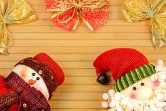 Bonhomme de neige et Santa sur un fond en bois photo libre de droits