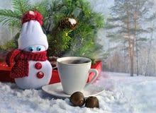 Bonhomme de neige fait main, tasse de café et sucrerie sur un fond neigeux de forêt Photographie stock