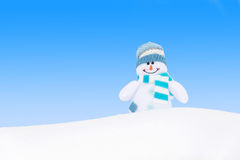Bonhomme de neige heureux d'hiver contre le ciel bleu Photographie stock libre de droits