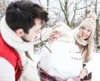 Bonhomme de neige heureux de bâtiment de couples Photographie stock libre de droits