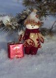 Bonhomme de neige mignon avec un cadeau sur la neige Images stock