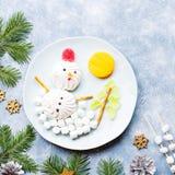 Bonhomme de neige de Noël fait de gelée de guimauve et de fruit sur un plat avec des branches et des décorations de sapin Vue sup photographie stock