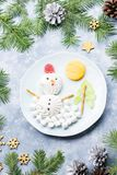 Bonhomme de neige de Noël fait de gelée de guimauve et de fruit sur un plat avec des branches et des décorations de sapin Vue sup photos libres de droits