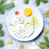 Bonhomme de neige de Noël fait de gelée de guimauve et de fruit sur un plat avec des branches et des décorations de sapin Vue sup photos stock