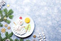 Bonhomme de neige de Noël fait de gelée de guimauve et de fruit sur un plat avec des branches et des décorations de sapin Vue sup image stock