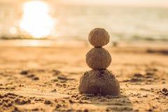 Bonhomme de neige de Noël de Sandy dans le chapeau et des lunettes de soleil rouges de Santa à la plage ensoleillée Concept de va photographie stock