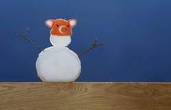 Bonhomme de neige se tenant sur un support de chêne un jour ensoleillé Photo libre de droits