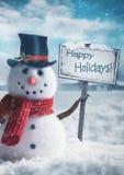 Bonhomme de neige tenant le signe en bois Photo libre de droits