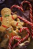 Bonhomme en pain d'épice de sourire sur le papier d'emballage avec le plan rapproché de canne de sucrerie Biscuits de Noël sur un photos stock