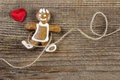 Bonhomme en pain d'épice et coeurs rouges mignons Photographie stock libre de droits