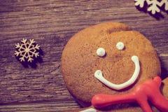 Bonhomme en pain d'épice sur le bois Le fond de vacances de Noël avec le biscuit de pain d'épice et les flocons de neige décorati Photo libre de droits