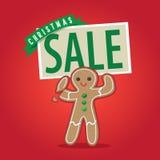 Bonhomme en pain d'épice tenant un signe de vente de Noël Photo stock